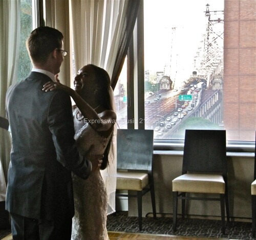 bride and groom dance with 59th Street bridge in back Round